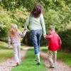 mother and two children walking on woodland path in autumn