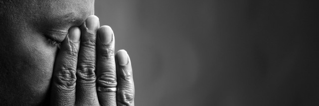 black and white photo of man holding his fingers over his nose