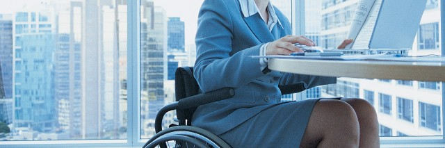 Businesswoman sitting in a wheelchair working on a laptop in the office.