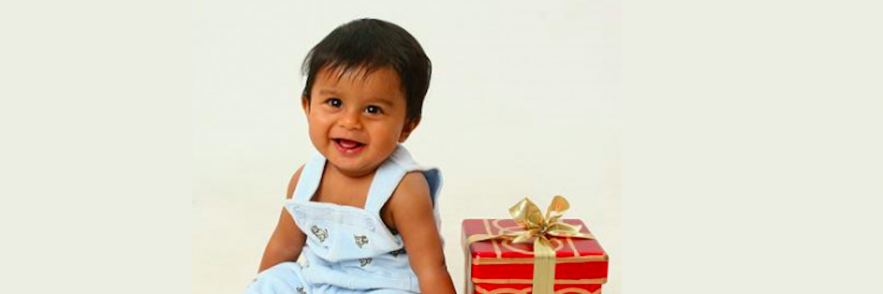baby boy sitting next to christmas present box