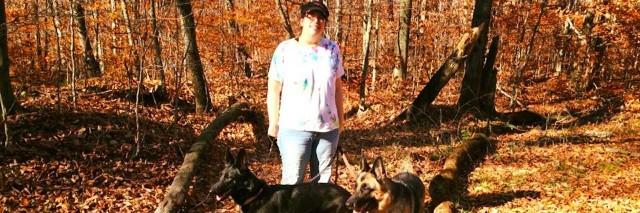 woman walking dogs in woods