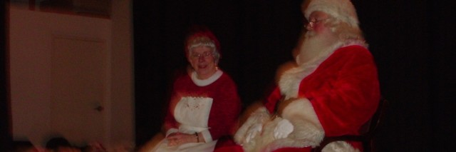 Santa Claus and Mrs. Clause sitting on a stage