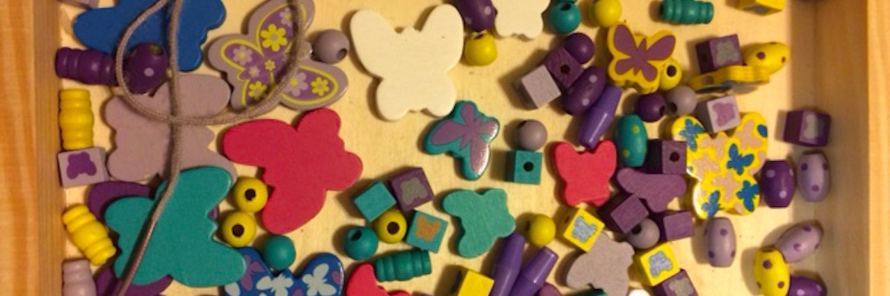 an array of differently colored and shaped beads in a tray