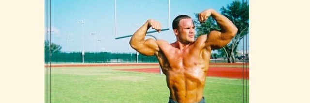 A body builder standing shirtless on a football field