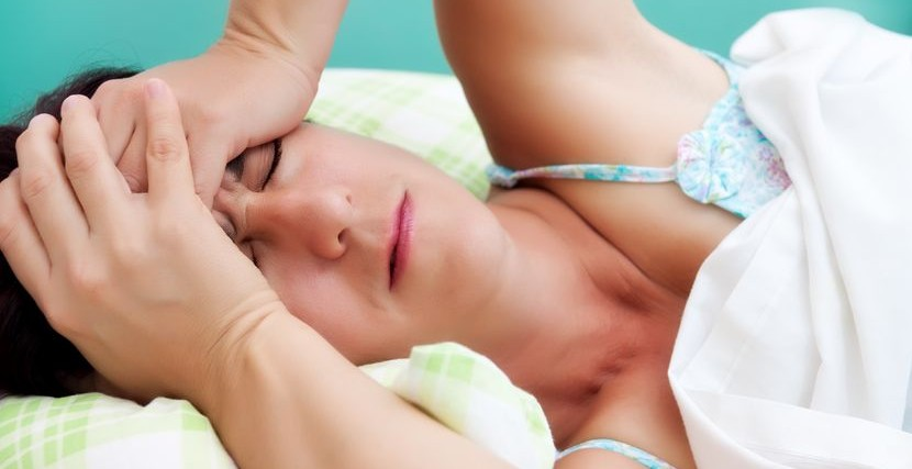 woman in bed with hands on her head