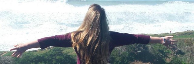 girl standing on cliff overlooking ocean with her arms outstretched