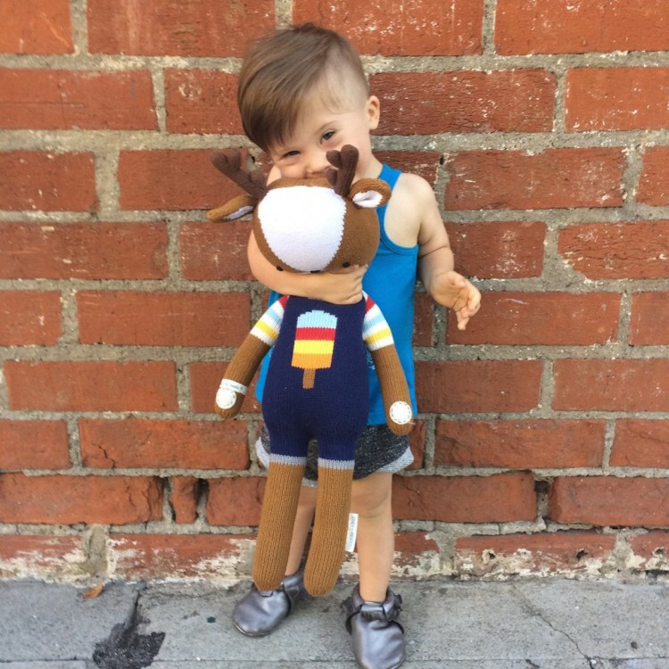 young boy holding stuffed toy in front of brick wall