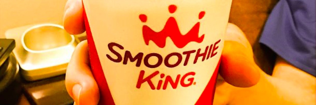 mans hand holding a styrofoam cup that says smoothie king