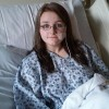 hannah wearing a hospital gown and laying in a hospital bed