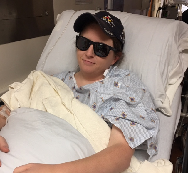 woman in a hospital bed wearing a baseball cap and sunglasses