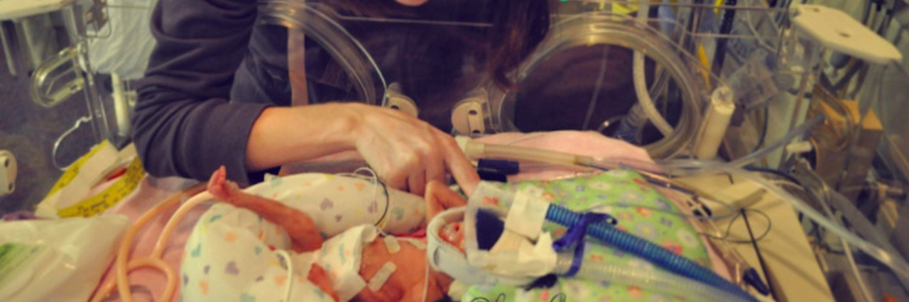 Mom looking at her baby in a NICU isolette