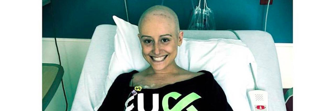 Woman in hospital bed wearing a shirt that says [f--- cancer]