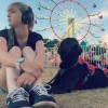 The author and her service dog sitting on the grass in front of a ferris wheel