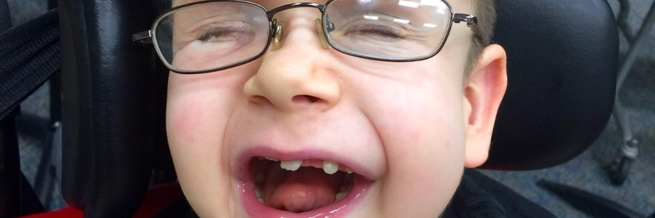 little boy smiling with mouth open wearing glassees