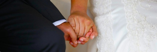 Husband and wife holding hands during a wedding ceremony