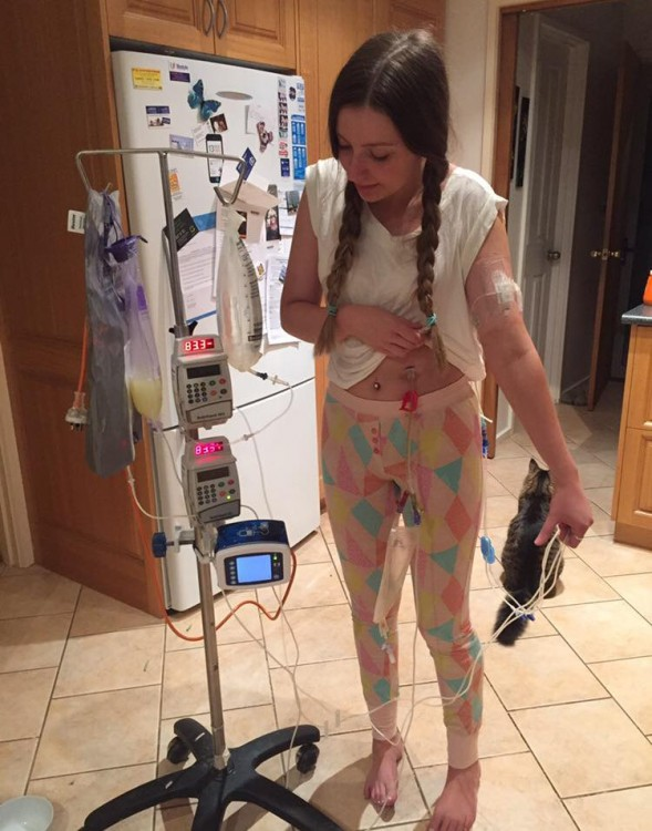 girl standing next to iv pole in kitchen
