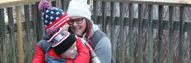 mother hugging two small children outdoors in winter gear