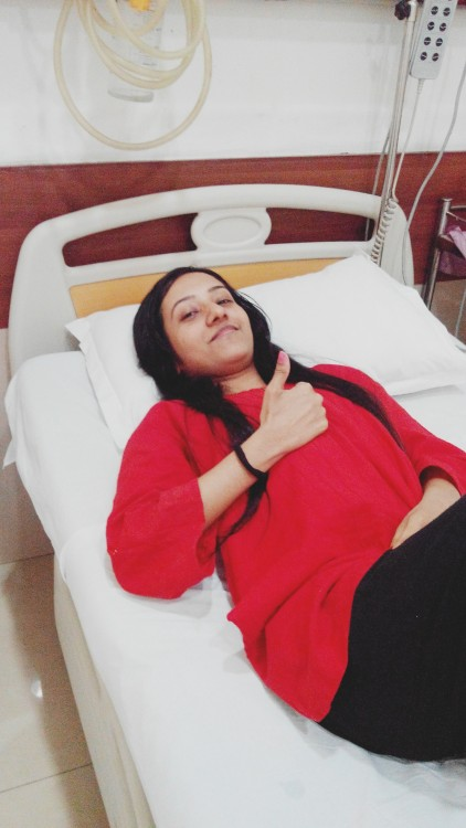 woman lying in hospital bed giving thumbs up sign
