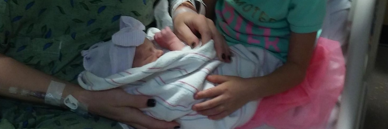 Woman holding newborn with daughter in hospital bed