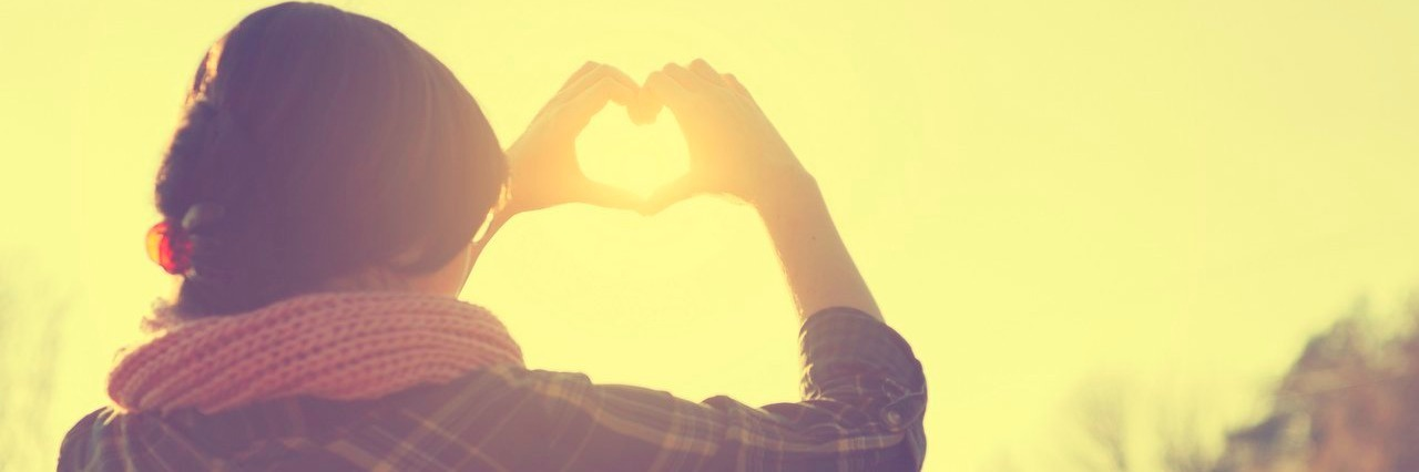 woman making heart symbol as the sun sets