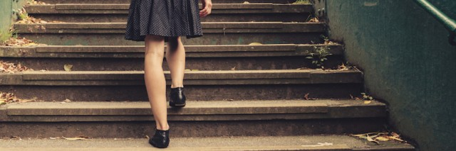 A young woman is walking up stairs outside in a park