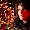 Young woman beside Christmas lights