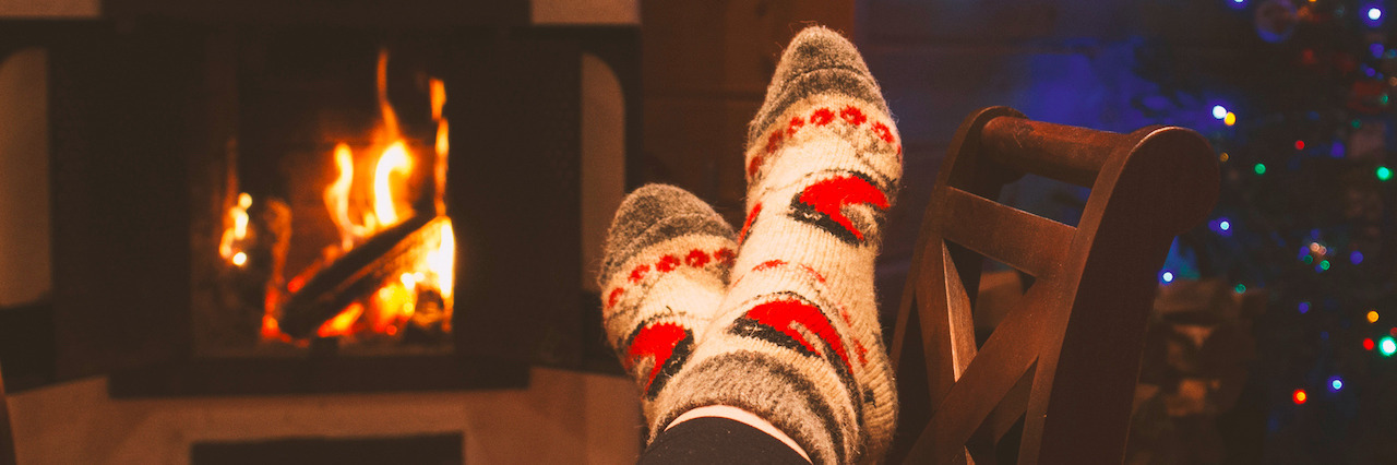 woman is warming her legs near the fireplace in winter socks during the cristmas holidays