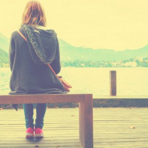 young woman sitting on a wooden pier