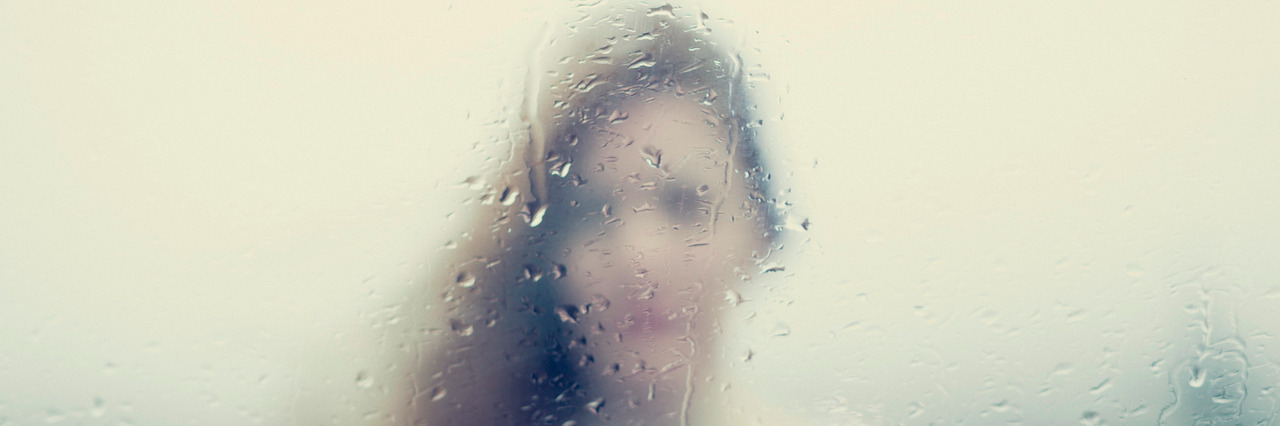 Blurry image of a woman through a rainy window