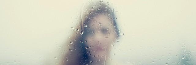 Blurry image of a woman through a rainy window