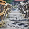 Closeup of a deformed and dilapidated wooden bridge over the small river. Weathered and broken wood planks of a very old and damaged pedestrian bridge near the village.
