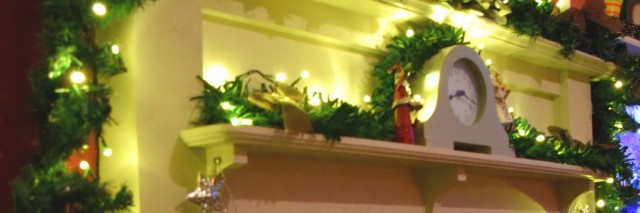 mantel decorated for christmas with garland, ornaments, and a santa