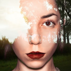 Double exposure portrait of young woman on a field with trees.