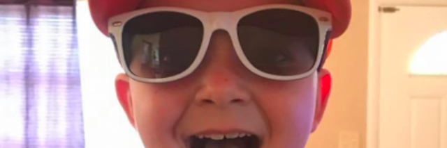 young boy in hat and sunglasses sticking his tongue out at the camera
