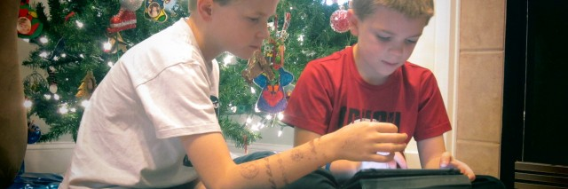 Children using a tablet by the Christmas tree.