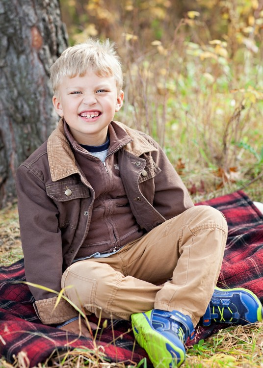 boy sitting in the woods and smiling