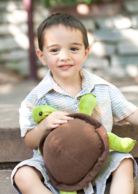 young boy holding stuffed turtle