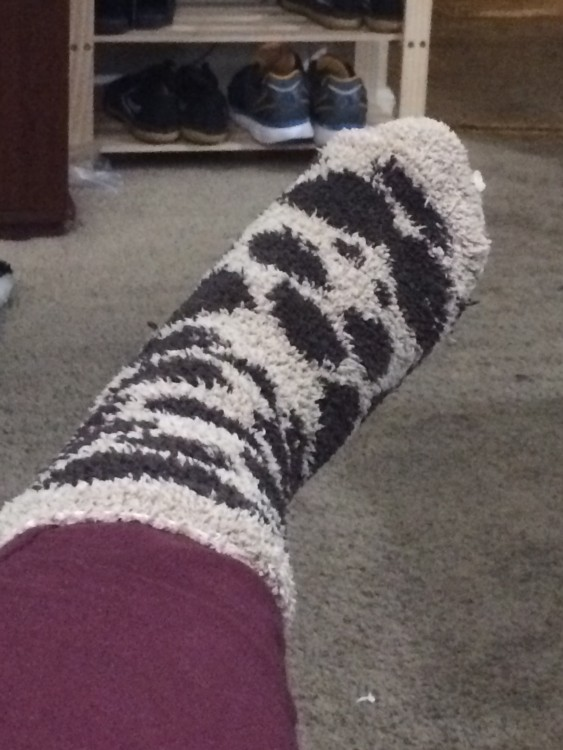 woman's foot with a fuzzy black and white polka dot sock