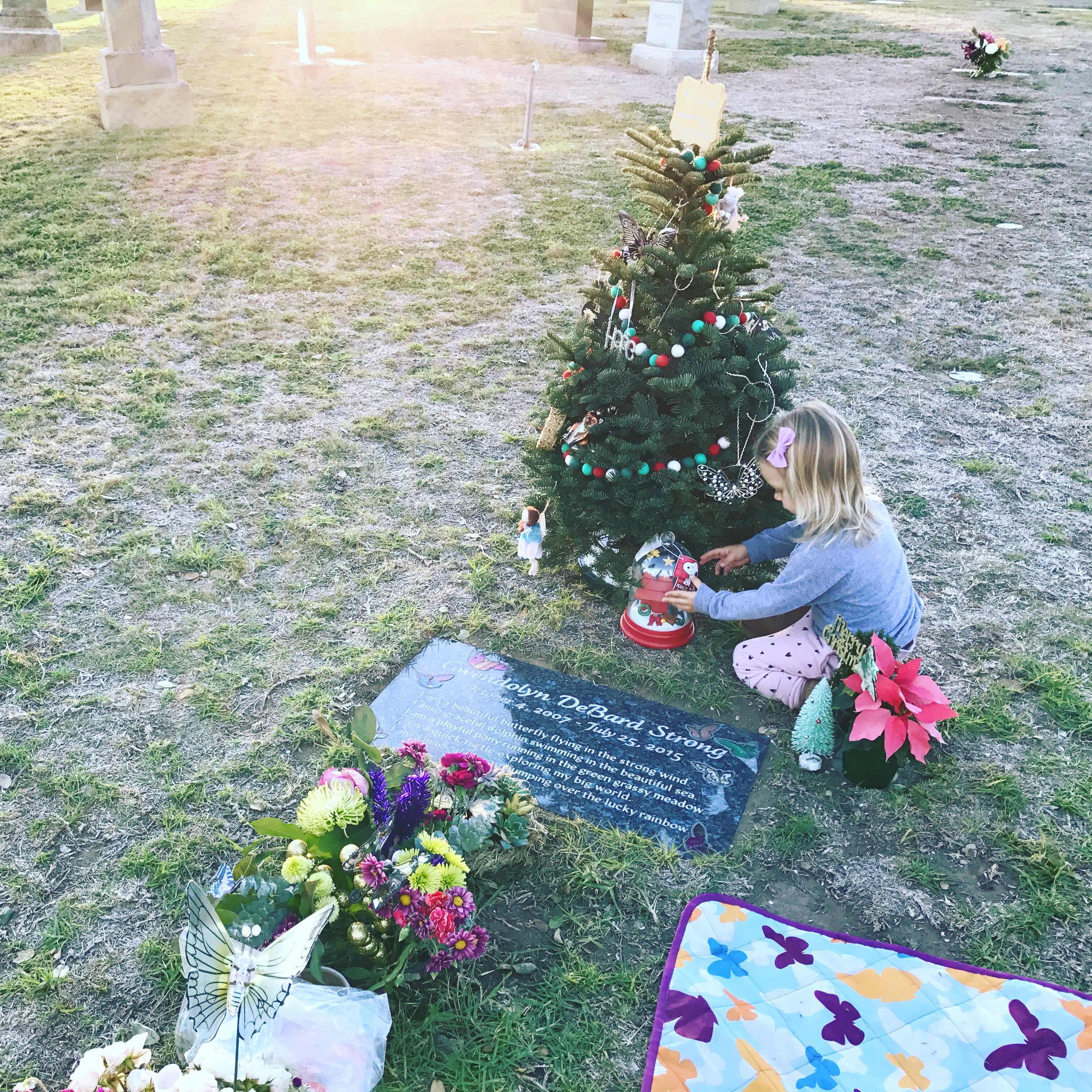The author's daughter decorating her sister's Christmas tree at the cemetery