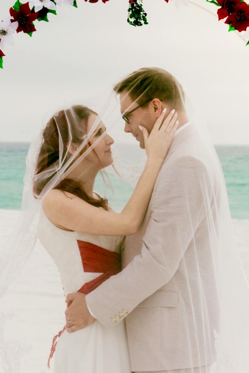 A groom and a bride embracing underneath her veil as they stand on the beach.