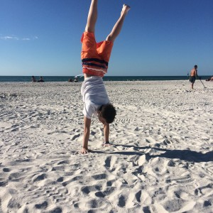 Erin's son doing gymnastics on the beach.