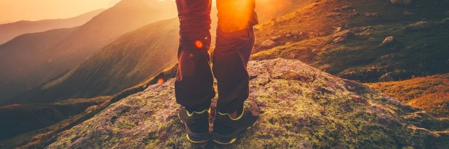 man hiking in the mountains and watching the sunset