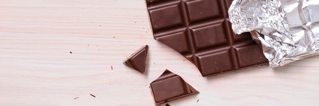 Detail of chocolate bar with silver wrapping on a wooden table with a broken portion. Horizontal composition. Top view