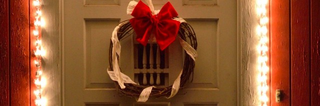 Christmas lights and wreath on front door at night