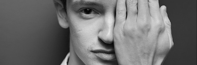 Young man with his hand covering half of his face