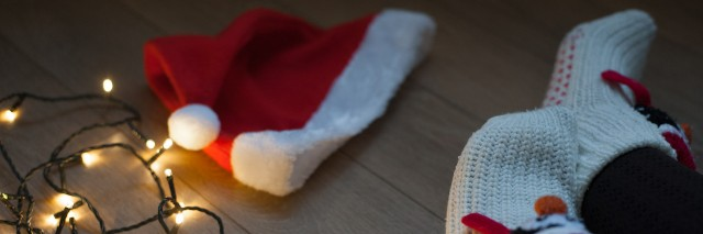 The night before christmas. Woman's legs and christmas hat on the floor. Preparation for holiday.