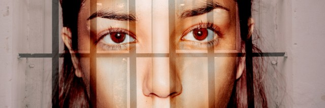 Double exposure portrait of young woman behind the bars