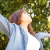 A young woman outdoors with her arms outstretched