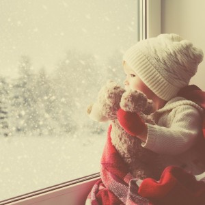 little girl with teddy bear looking out a window during winter