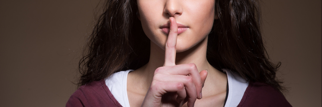Beautiful young girl making silence gesture with finger over lips